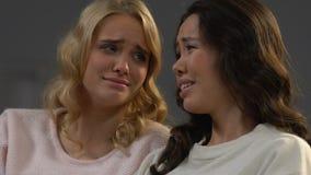 Tacto de las mujeres que inclinan a las cabezas que miran series de drama en la TV y que lloran, emociones almacen de metraje de vídeo