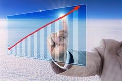 Tacto de una flecha de la tendencia del crecimiento en una carta de barra Foto de archivo libre de regalías