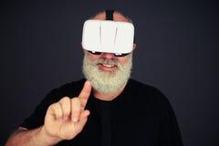 Tacto del hombre mayor algo auriculares de alta tecnología de VR que llevan Imagenes de archivo
