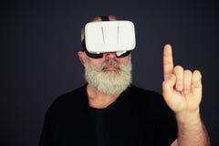 Tacto del hombre mayor algo usando los vidrios de la realidad virtual Imagenes de archivo