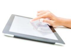 Tacto femenino de la mano del primer en la pantalla de la tableta en blanco Fotos de archivo