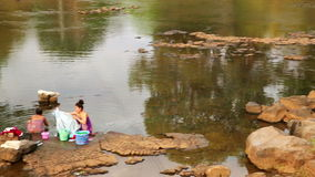 TAD LO, LAOS - MARCH 2014: Women washing clothes at river,. Traditional laundry village life stock video