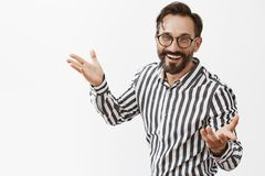 Tada. Portrait of charming confident and happy male entrepreneur in striped shirt and glasses, gesturing with palms in. Self-assured and friendly pose and royalty free stock photo