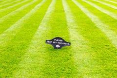 Tadellos gestreifter frisch gemähter Gartenrasen mit einem Warnzeichen stockfoto