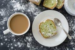 Tadelloser Kuchen besprüht mit Puderzucker auf dunkler Oberfläche mit Tasse Kaffee Stockfoto