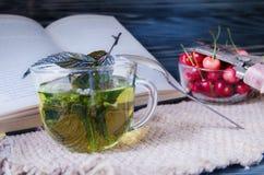 Tadelloser Tee in einer Glasschale mit Kirschen Stockbilder