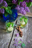 Tadelloser Tee und lila Blumen Stockbilder