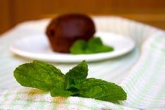 Tadelloses Blatt-und Schokoladen-Muffin auf der Untertasse im Hintergrund Lizenzfreie Stockfotos