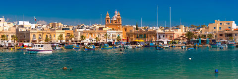 Taditional eyed boats Luzzu in Marsaxlokk, Malta. Panorama with traditional eyed colorful boats Luzzu in the Harbor of Mediterranean fishing village Marsaxlokk Royalty Free Stock Photography