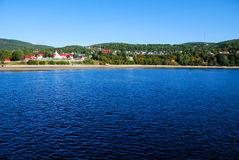 tadoussac海湾看法在从一艘渡轮的加拿大在蓝天和水背景 免版税库存图片