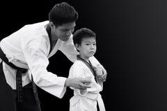 Taekwondo master black belt teaching kid to fight guard stand. Taekwondo master black belt sport teaching kid to fight guard on black background stock photos