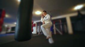 Taekwondo utbildning med att stansa påsen, backlit långsamt arkivfilmer