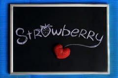 Tafel auf blauem Hintergrund, Kreidebeschriftung und Erdbeerherzen formte Lizenzfreies Stockfoto