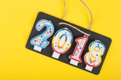 Tafel auf dem Seil mit der Aufschrift 2018 machen von den Kerzen auf einem gelben Hintergrundpapier stockbild