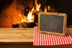 Tafel auf Holztisch über Kaminhintergrund Winter- und Weihnachtsfeiertag stockfotografie
