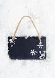 Tafel auf Schnee mit Schneeflocken Stockfotos
