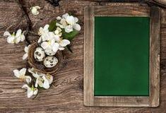 Tafel, Blumen und Ostern nisten mit Eiern Lizenzfreies Stockfoto