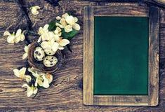 Tafel, Blumen und Ostern nisten mit Eiern auf hölzernem backgrou Stockbilder