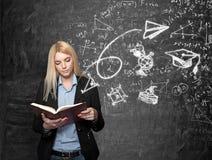 Tafel des jungen Mädchens Lesemit Wissenschaftsikonen am backgrou Lizenzfreies Stockfoto