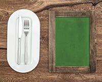 Tafel für Menü oder Rezept Grüne Tafel mit weißer Platte Stockfotografie
