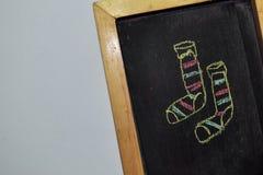 Tafel im Holzrahmen auf weißem Hintergrund mit Handgezogenen Gekritzel-Weihnachtssocken stockfoto