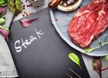 Tafel mit Aufschrift Steak, rohem Rindfleischsteak und Bestandteilen für Grill oder BBQ auf rustikalem Küchentisch, Draufsicht Stockbilder