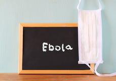 Tafel mit dem Wort ebola geschrieben auf es und Gesichtsmaske Stockfoto