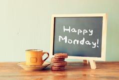 Tafel mit der Phrase glücklicher Montag nahe bei Tasse Kaffee und Plätzchen Stockbilder