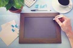 Tafel mit Grünpflanze und Büroartikel stockfotografie