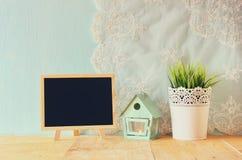 Tafel mit Raum für Text, Weinlese Blumentopf und Laterne als Vogelhaus gegen tadellose Wand und Antike schnüren sich Gewebe Lizenzfreie Stockbilder