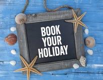 Tafel mit Seedekoration auf blauem hölzernem Hintergrund mit Buch Ihr Feiertag stockfoto