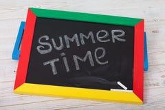 Tafel mit Text ist es Sommerzeit auf hölzerner Plattform Stockbild