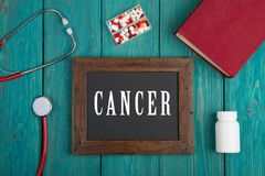 Tafel mit Text u. x22; Cancer& x22; , Buch, Pillen und Stethoskop auf blauem hölzernem Hintergrund stockbild