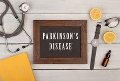 Tafel mit Text u. x22; Parkinson& x27; s-disease& x22; , Buch, Stethoskop und Uhr Lizenzfreie Stockfotos
