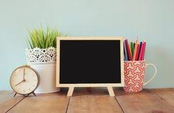 Tafel, Stapel bunte Bleistifte und Uhr Zurück zu Schule-Konzept Lizenzfreie Stockbilder