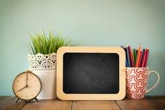 Tafel, Stapel bunte Bleistifte und Uhr Zurück zu Schule-Konzept Lizenzfreies Stockbild