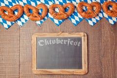 Tafel und Brezel auf hölzernem Hintergrund für Oktoberfest-Feier stockfotos
