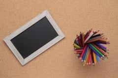 Tafel und farbige Bleistifte Stockbilder