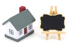 Tafelaufkleber und Miniaturmodell des Hauses lokalisiert auf Weiß Lizenzfreie Stockfotografie