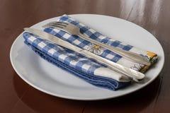 Tafelsilber auf dem Geschirrtuch, der Metallgabel und dem Messer auf der weißen Platte mit dishtowel Lizenzfreie Stockbilder