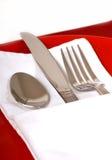 Tafelsilber in einer gefalteten Serviette auf einer roten Platte Lizenzfreie Stockfotos