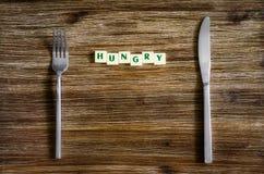Tafelsilber eingestellt auf Holztisch mit Zeichen hungrig Lizenzfreie Stockbilder