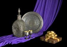 Tafelsilber und das Geschenk sind auf dem drapierten Gewebe Stockfoto