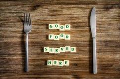 Tafelzilver op lijst en Goed voedsel gediend hier teken stock afbeelding