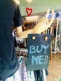 """Buy me please. A tag """"buy me"""" invites people whose shopping clothes in markets royalty free stock photo"""