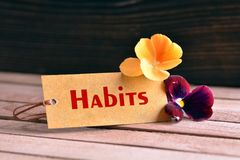 Habits tag. Tag banner habits and violet flower on wooden desk Royalty Free Stock Image