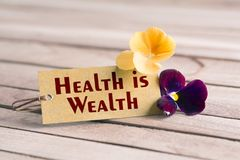 Health is wealth tag. Tag banner health is wealth and violet flower on wooden desk Stock Photos