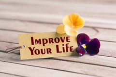 Improve your life tag. Tag banner improve your life and violet flower on wooden desk Royalty Free Stock Photography