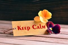 Keep calm tag. Tag banner keep calm and violet flower on wooden desk stock photo