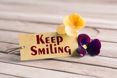 Keep smiling tag. Tag banner keep smiling and violet flower on wooden desk Royalty Free Stock Photo